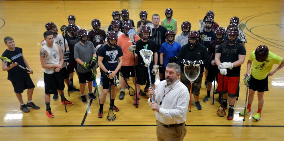 Chris Hopkins, head coach of the combined Maine Central Institute and Nokomis boys lacrosse team, poses with his players this week in Pittsfield.