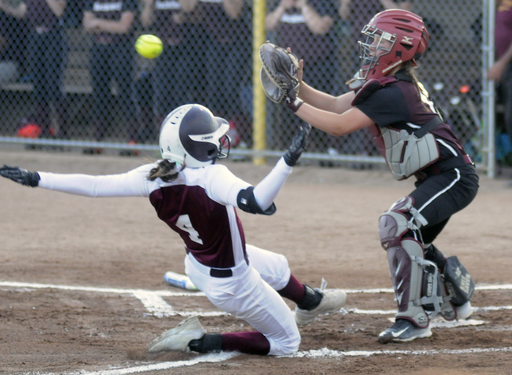 Richmond runner Meranda Martin slides safely into home under as Buckfield catcher Hannah Shields awaits the throw during the Class D South title game last season at St. Joseph's College in Standish.