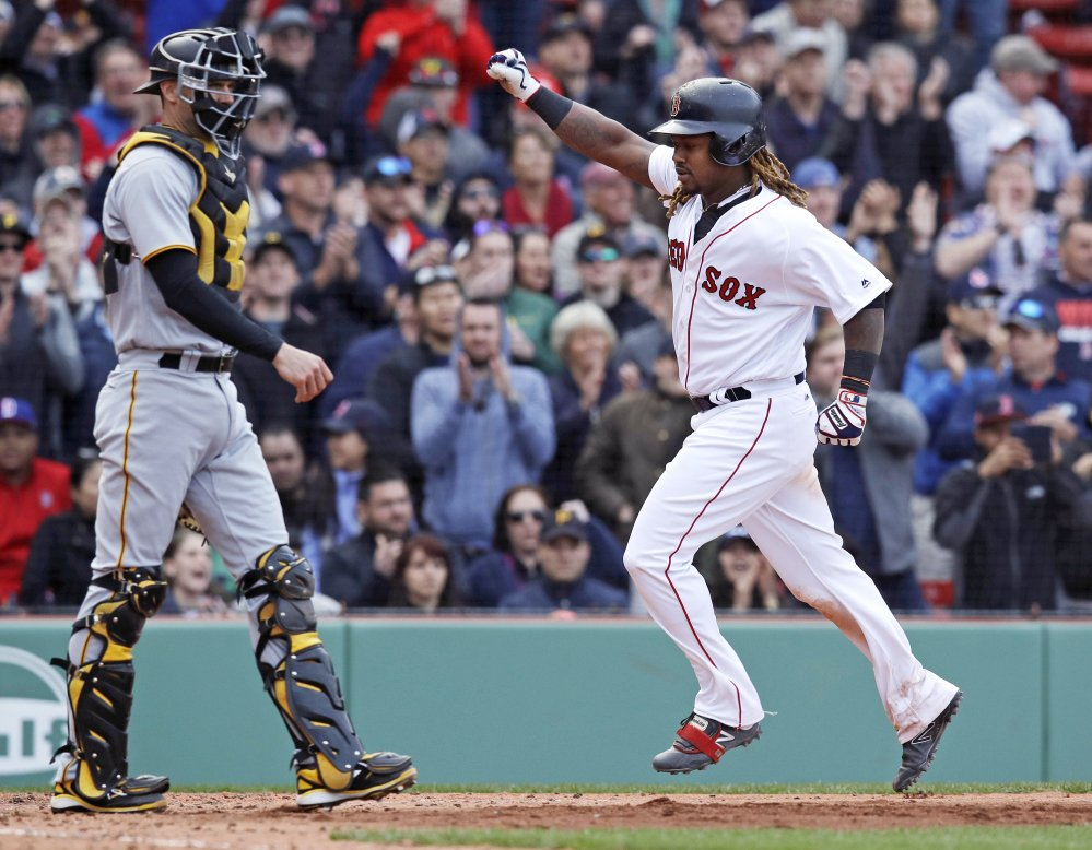 Boston's Hanley Ramirez, right, pumps his fist as he passes Pittsburgh catcher Chris Stewart, left, while scoring on an RBI single by Xander Bogaerts during the eighth inning Thursday in Boston.