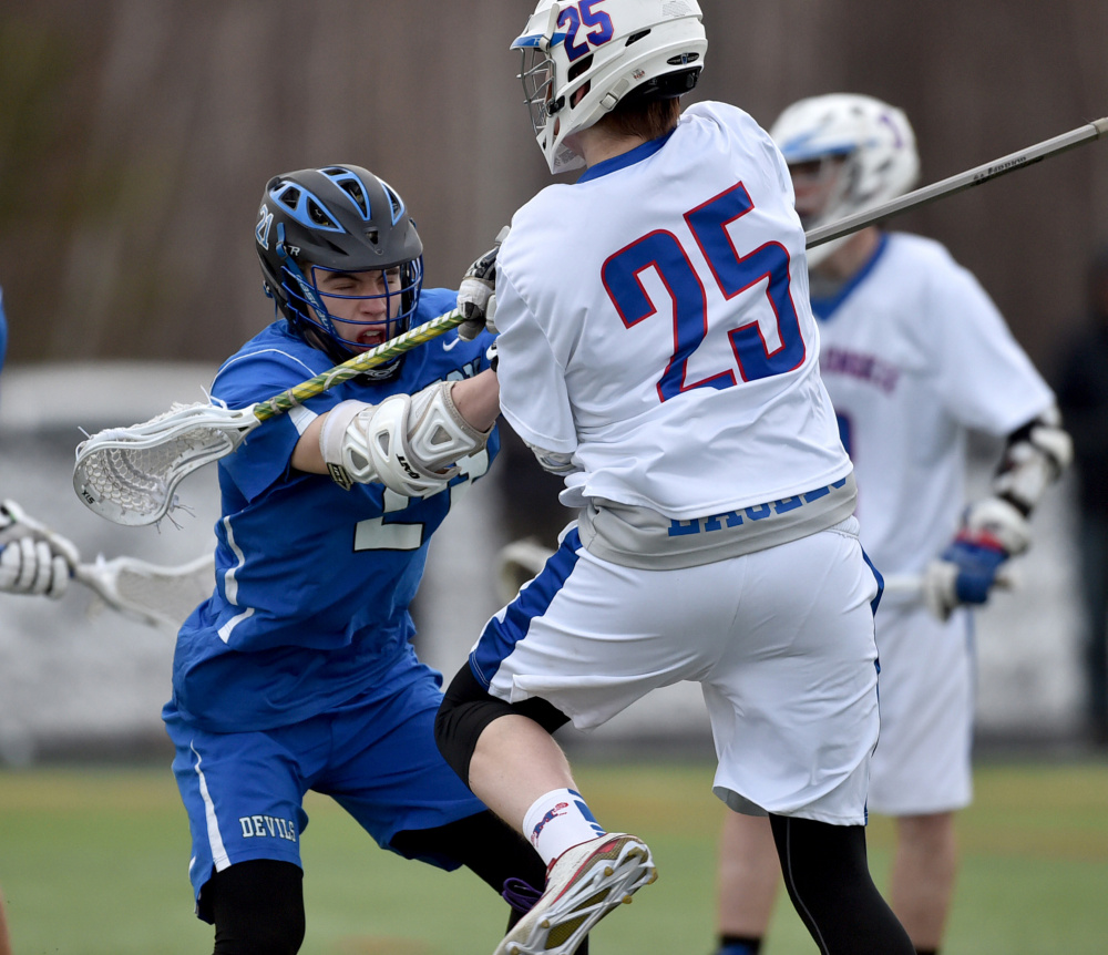Messalonskee's Trevor McCray (25) battles with Lewiston's Ryan McCarthy during a game Thursday at Thomas College in Waterville.