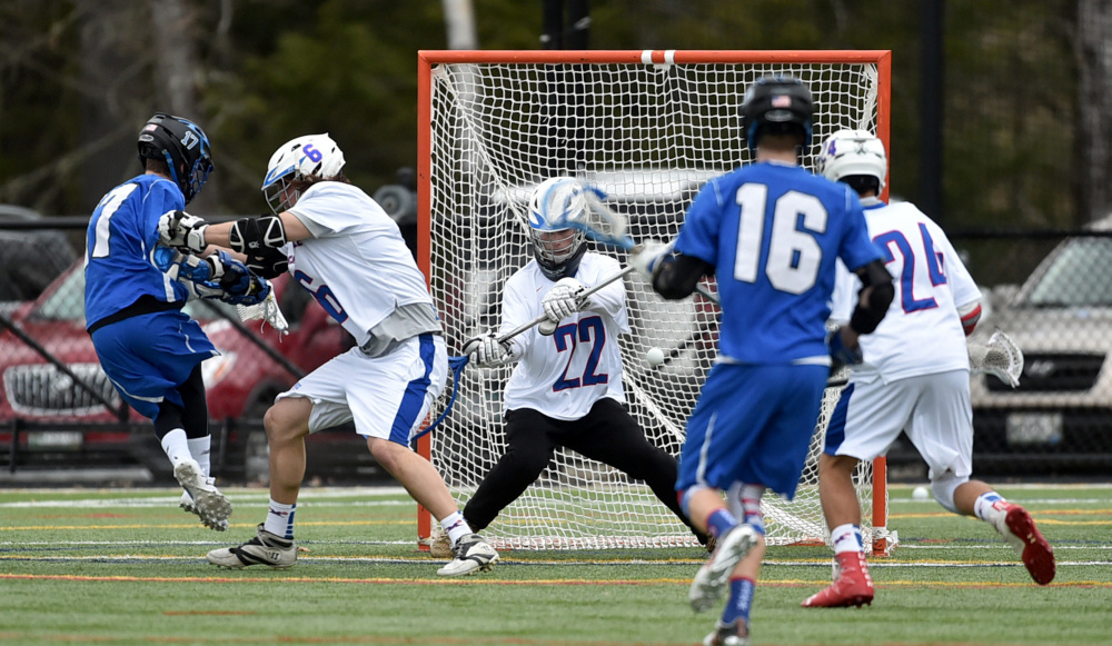 Messalonskee goalie Dawson Charles (22) makes a save on a shot by Lewiston's C.J. Reardon, far left, who is hit by Messalonskee's Dylan Gagne on Thursday at Thomas College in Waterville.