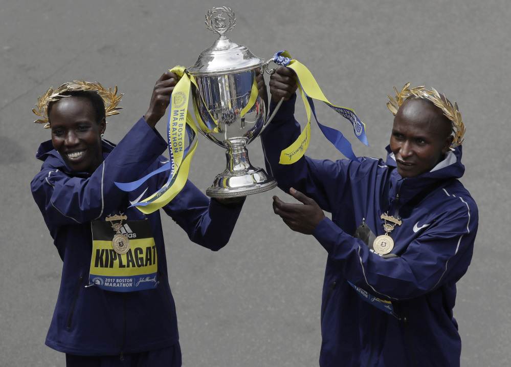 Edna Kiplagat, left and Geoffrey Kirui, both of Kenya, hold a trophy together after their victories in the 121st Boston Marathon on Monday in Boston.