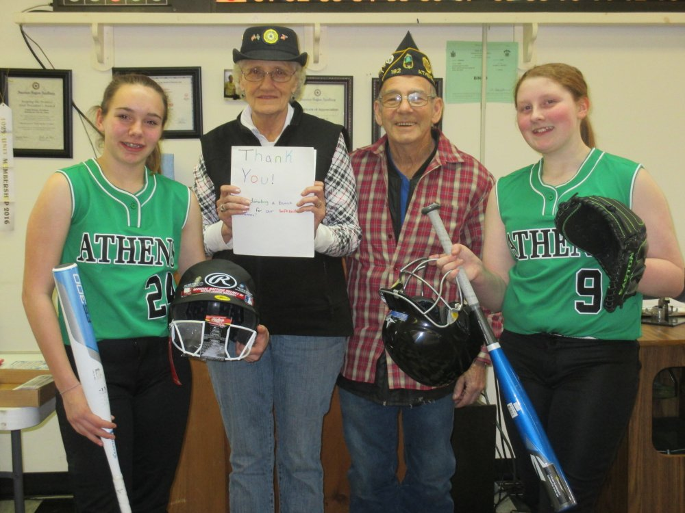 Captains of the Athens Community School softball team, wearing new uniforms and holding new equipment bought with donations from American Legion Post 192 and its Ladies Auxiliary, present the organizations' presidents a thank-you card. From left are Captain Kira Braley, presidents Robert Doiron and Linda Doiron, and Captain Kaitlyn Pomelow.