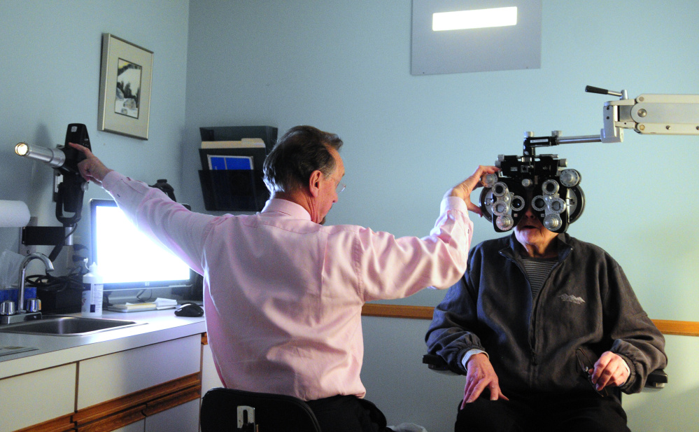 Dr. Kenneth Nuzzo adjusts the projector displaying a test chart and the lens on the phoropter in January while doing an examination of Julie Bernier at his office. Nuzzo, who is retiring, is selling his practice to Vision Care of Maine.