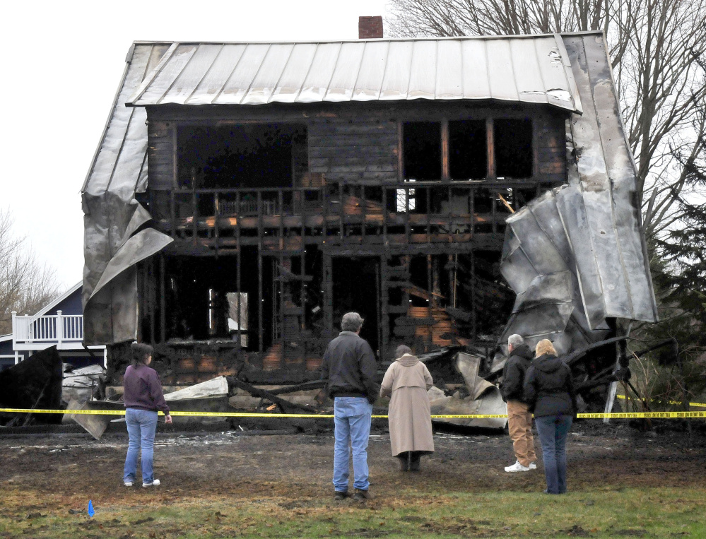 People survey the remains of a home Thursday morning on Main Street in Vassalboro that was destroyed by fire the previous night.