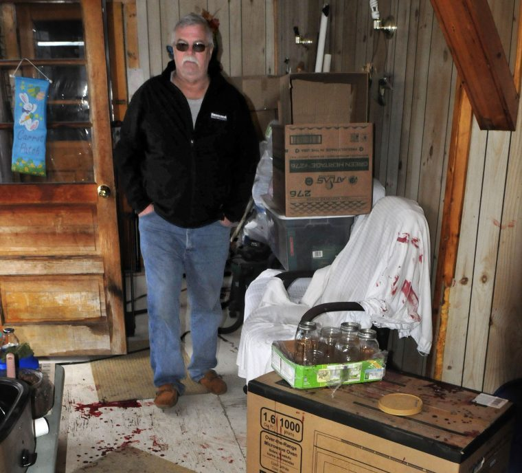 On Thursday, David Grant surveys the enclosed porch and breezeway in his neighbors' home at 230 Oak St. in Oakland, where blood was splattered on the floor and the walls. Jeremy Clement allegedly entered the home Wednesday evening and shot Jasmine Caret before her mother, Roseanna Caret, subdued Clement with a bat and then police arrived and arrested him. Grant assisted police in the arrest.