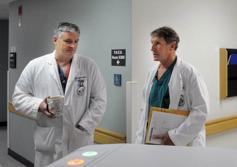 Dr. William Curtis, left, and Dr. Cameron McKee speak July 11, 2016, on the surgical floor of VA Maine Healthcare Systems-Togus during a tour of the veterans hospital, which has made significant improvements in mental health care, according to a new federal report.