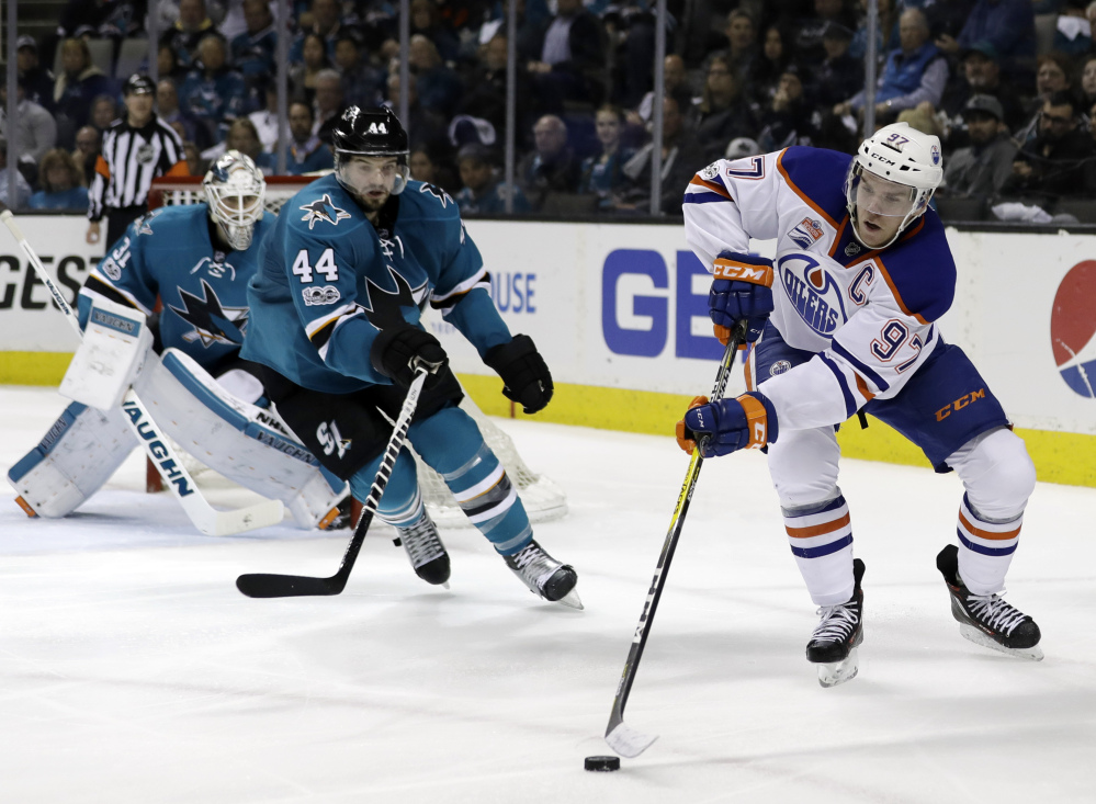 Edmonton Oilers phenom Connor McDavid (97) reaches for the puck next to San Jose Sharks' Marc-Edouard Vlasic (44) during the second period of Game 4 on Tuesday.
