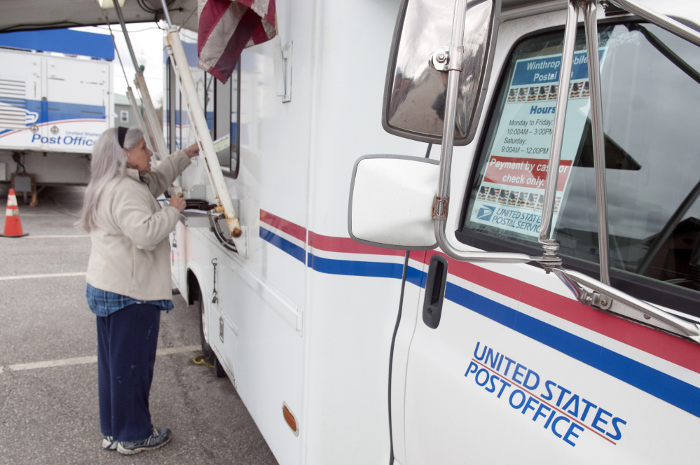 Mary Dyer conducts her postal business Thursday at a mobile post office truck in downtown Winthrop. The truck is set up in the parking lot of the old post office, which burned on Feb. 21.