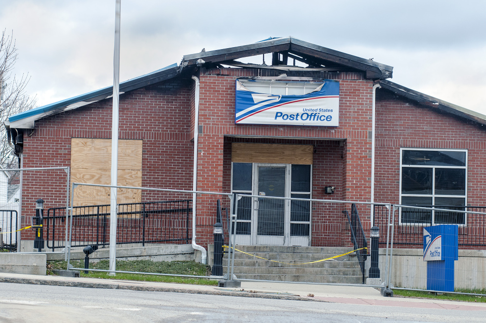 The burned-out Winthrop post office, seen Thursday, is expected to be demolished. A mobile post office truck is conducting U.S. Postal Service business in the back parking lot.