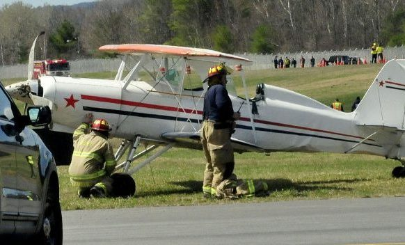 Waterville police and firefighters arrive at the scene of a reported overturned aircraft at the Waterville Airport on Sunday. Police say strong wind caused the bi-plane, piloted by Keith Deschambeault of Rangeley, to partially overturn while landing. Deschambeault was not injured and the plane was damaged. In background are members of statewide fire and rescue departments that were present for unrelated training.