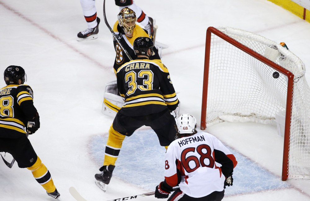 Boston goalie Tuukka Rask, top, and Zdeno Chara (33) watch the shot by Ottawa's Clarke MacArthur, not shown, enter the net during overtime in Game 6 of a first-round Stanley Cup playoff series Sunday in Boston.