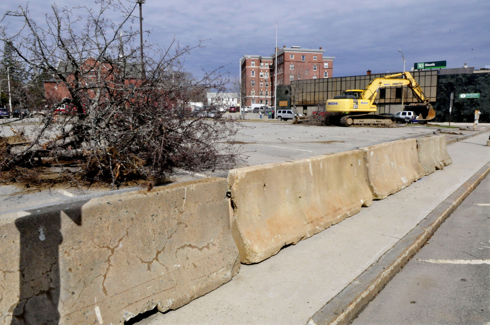 Concrete barriers were placed around the site where construction on the Colby College multi-use residential building is beginning in The Concourse in Waterville Monday. In the background an excavator rips a live tree from the pavement.