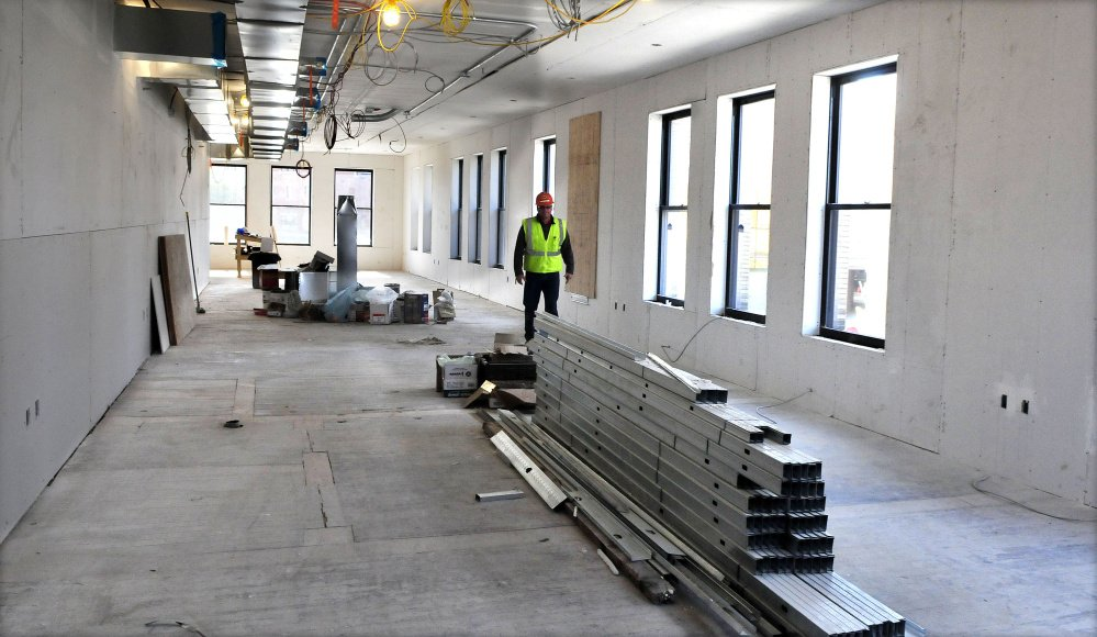 Ken Theriault, superintendent of P.C. Construction, walks past new windows and construction of new space on the second floor of the former Hains building in downtown Waterville on Monday.