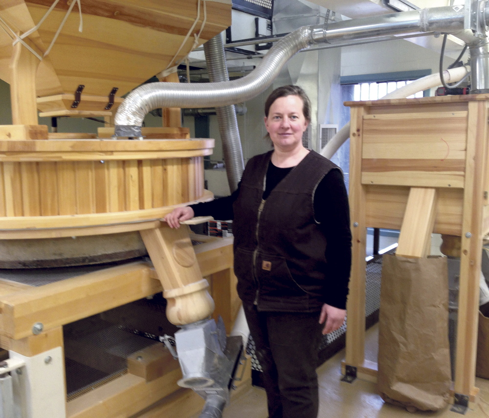 Amber Lambke stands beside a working mill grinding flour April 30, 2014, at the Somerset Grist Mill in Skowhegan. Lambke, president of Maine Grains, is the first speaker in Thomas College's series on entrepreneurship and innovation.