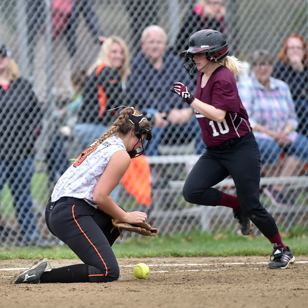 Winslow first baseman Natalie Greene, left, comes of the bag to reel in an errant throw as Nokomis' Hanna Meservey (10) reaches safely Thursday in Winslow.