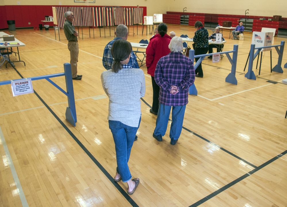 Staff photo by Joe Phelan Voters wait in line at 7:59 a.m. Friday for polls to open at 8 a.m. for the bond vote in the Hall-Dale Elementary School gymnasium in Hallowell.