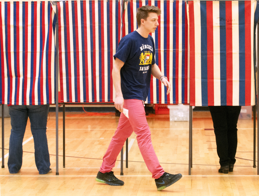 First-time voter Jett Boyer, who recently turned 18, walks toward a ballot box around 8:10 a.m. Friday in the Hall-Dale Elementary School gymnasium in Hallowell. Boyer, a Hall-Dale High School student, was missing part of government class to get registered and vote.
