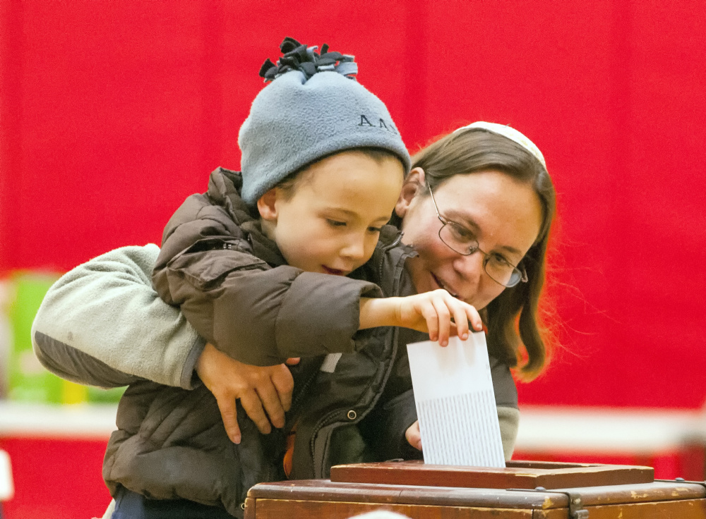 Aaron Asch, 4, drops a bond vote ballot for his mother, Rabbi Erica Asch, just after 8 a.m. Friday in the Hall-Dale Elementary School gymnasium in Hallowell.