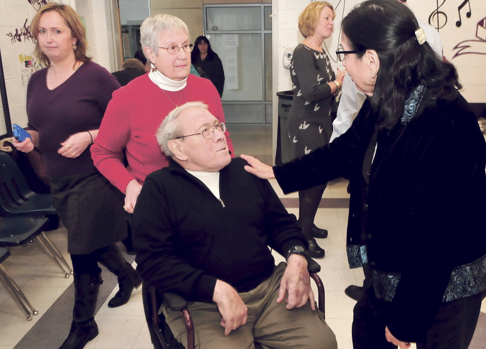 Joan Phillips-Sandy, right, congratulates retiring Waterville School Board member and chairman Lionel Cabana during an event honoring him Dec. 8, 2014. Behind Lionel is his wife, Judy, and at left is Susan Reisert who filled the Ward 2 board member position.