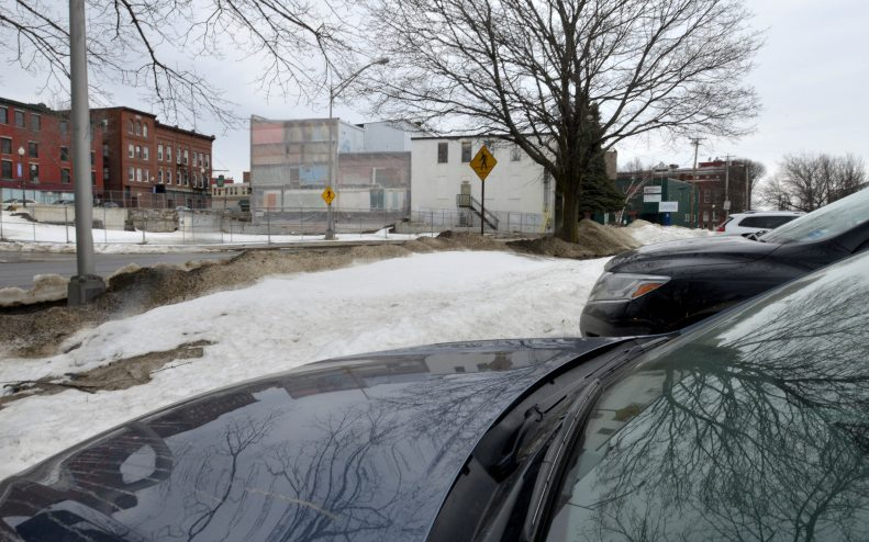 Cars in a proposed parking lot for Colby College sit in front of the empty lot that will soon be home to a boutique hotel on Front Street in Waterville on March 21  Waterville City Council is expected to take a final vote on leasing parking spaces from the city for the hotel Tuesday.