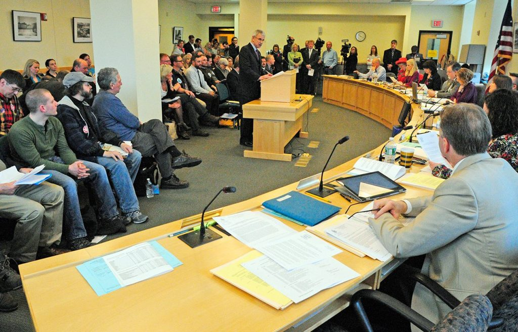 "As a standing-room-only crowd looks on, Sen Roger Katz introduces ""An Act To Restore the Tip Credit to Maine's Minimum Wage Law"" during a hearing of the Labor, Commerce, Research and Economic Development Committee on Wednesday."