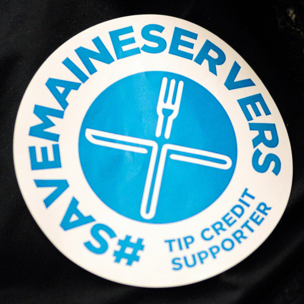Supporters of changes to Maine's tip credit rules wore blue stickers for Wednesday's legislative hearing.