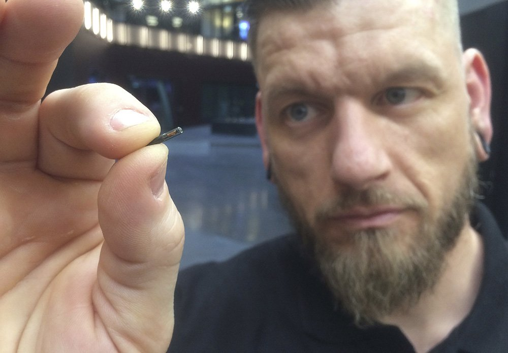 "Self-described ""body hacker"" Jowan Osterlund from Biohax Sweden holds a microchip implant similar to those implanted into workers at the Epicenter digital innovation business center."