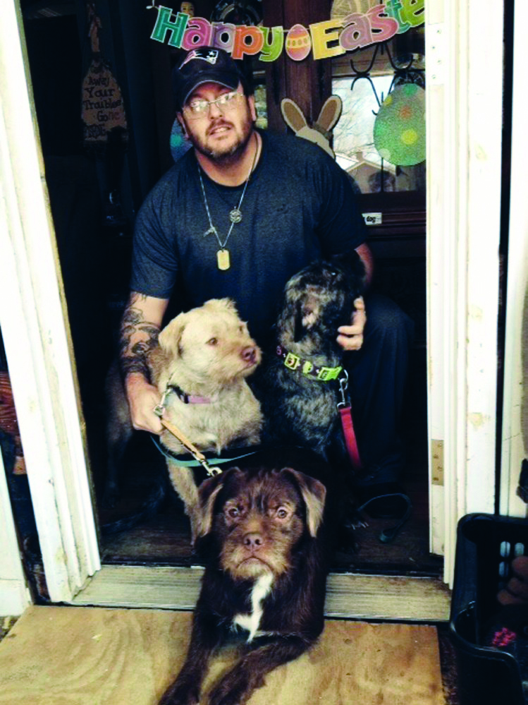 Paul Mann Sr. and three dogs — Flower, Brownie and Sofia — are seen at his Western Avenue home in Waterville on Friday.