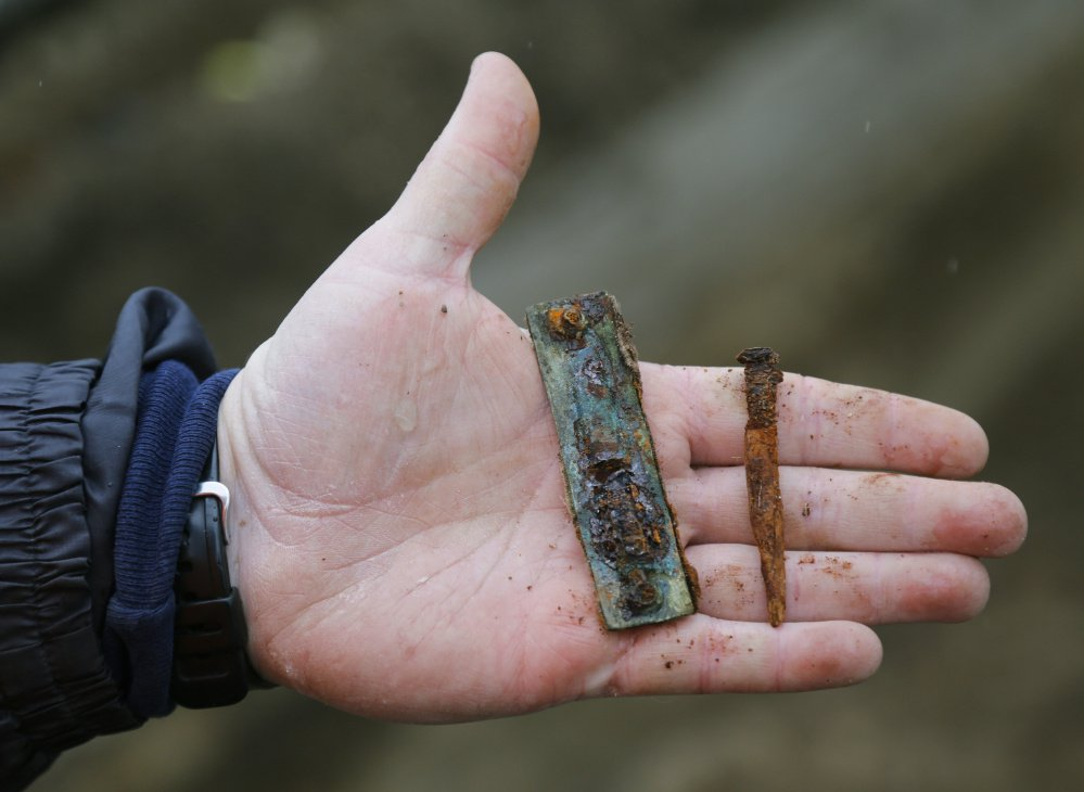 Paul Auger holds a nail and a bracket from a grave discovered at a construction site on Main Street. Auger estimates that the grave is from sometime between 1880 and 1906.