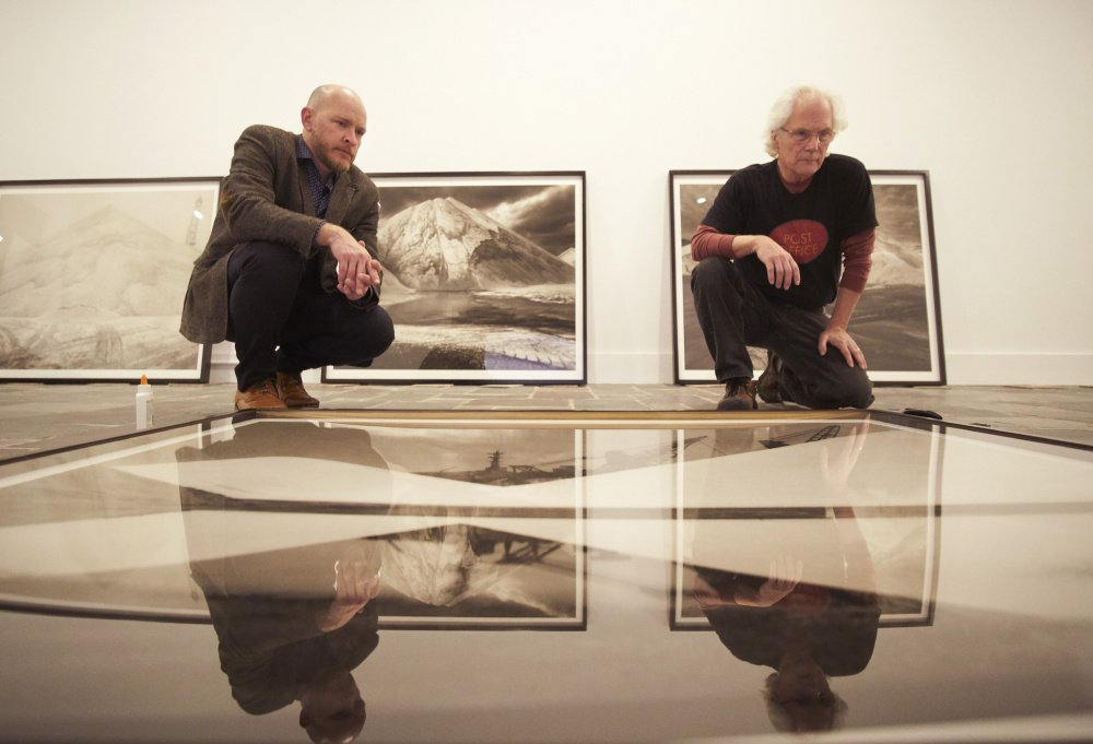 "Michael Mansfield, left, the new executive director and chief curator at the Ogunquit Museum of American Art, examines a photograph with Carl Austin Hyatt in preparation for ""Salt/Sea/Stone,"" an exhibition of Hyatt's large-scale images."