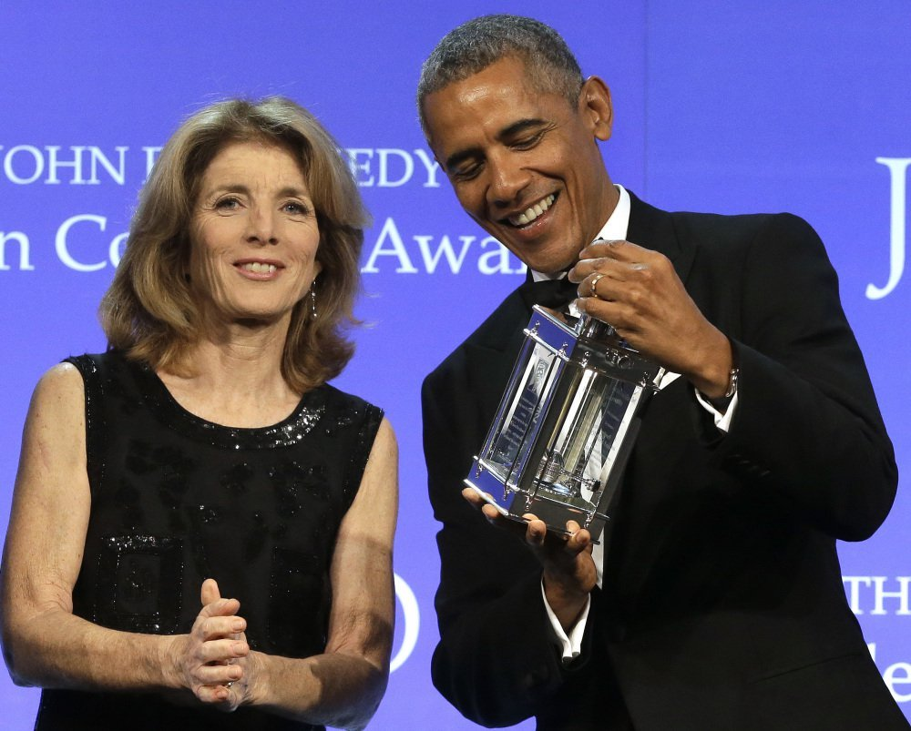 Former President Barack Obama accepts his Profile in Courage award from Caroline Kennedy in Boston on Sunday. Obama called on Congress to show courage of its own.