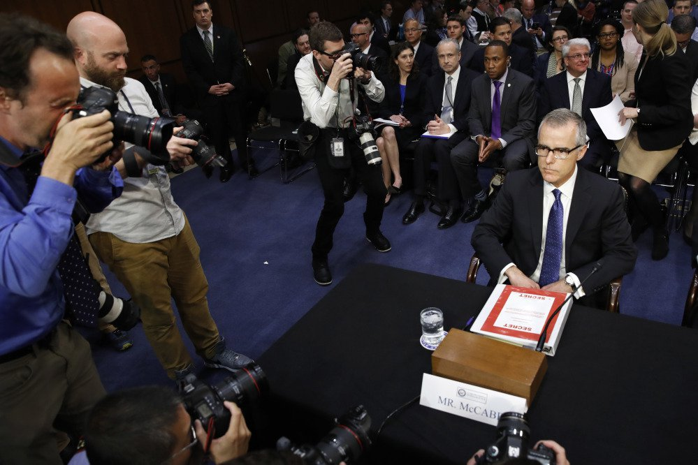 "Photographers surround acting FBI Director Andrew McCabe as he takes his seat with a folder marked ""Secret,"" on Capitol Hill in Washington on Thursday before testifying before the Senate Intelligence Committee."