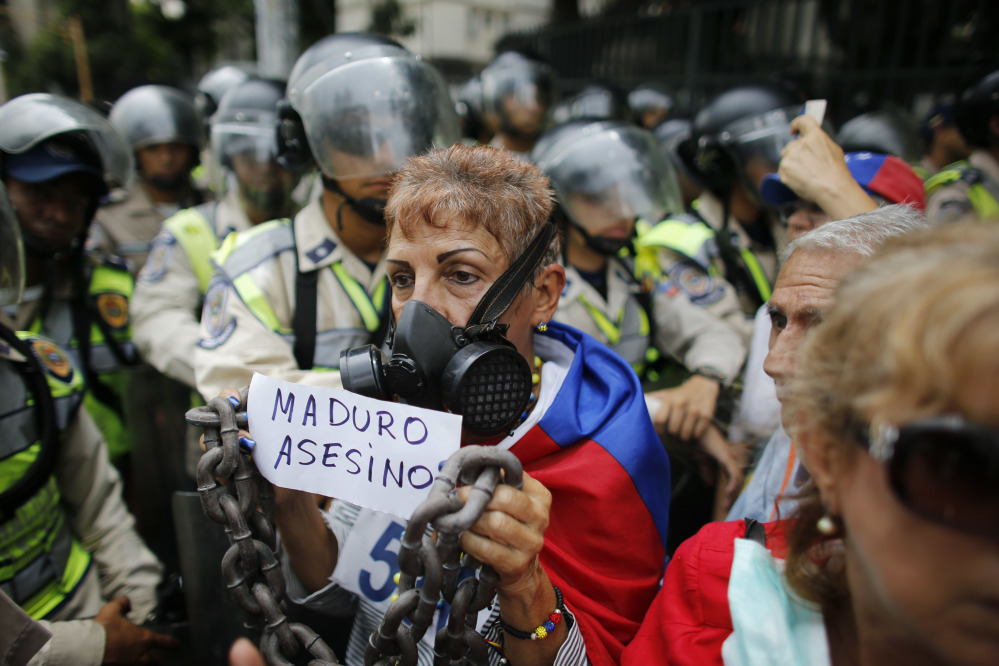 "A woman holds a handwritten message that reads in Spanish: ""Maduro Murderer"" during a protest against President Nicolas Maduro in Caracas, Venezuela, on Friday."