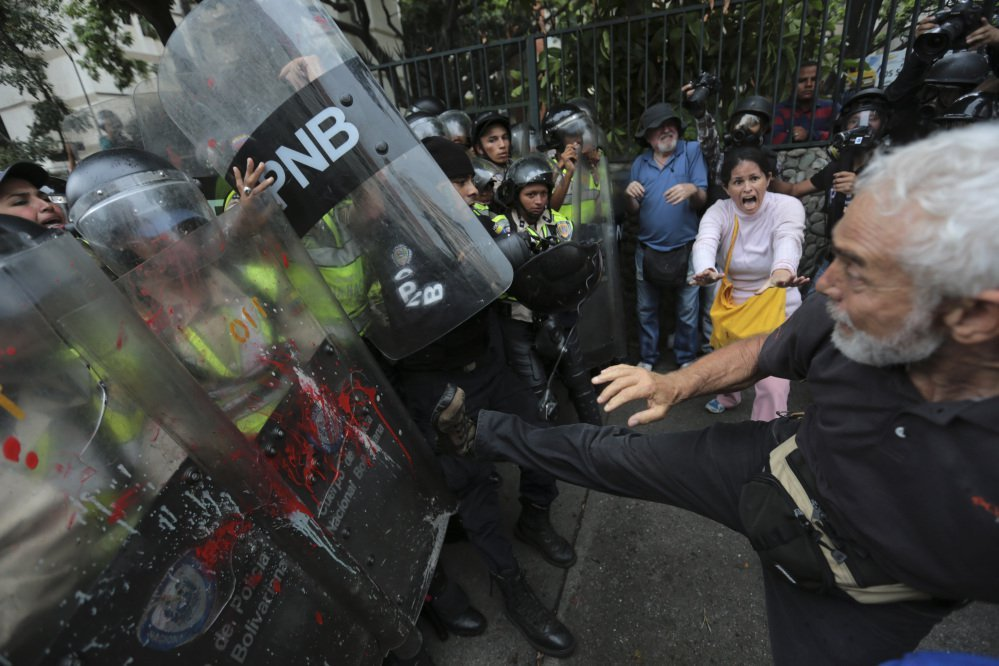 "An anti-government protester kicks at riot police blocking a march of elders against President Nicolas Maduro in Caracas, Venezuela, on Friday. The protest billed as the ""March of the Grandparents"" comes after six weeks of political unrest."