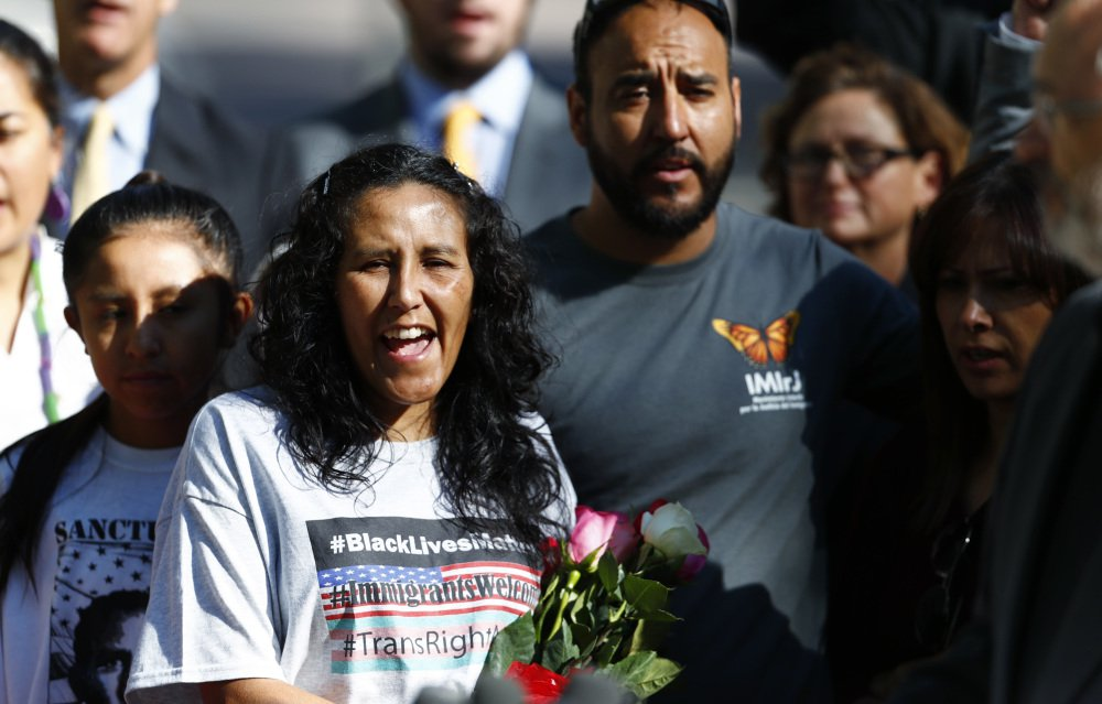 Jeanette Vizguerra, left, leaves a church Friday where she lived to avoid immigration authorities for the past three months. She and Arturo Hernandez, center, are both Mexican immigrants who have been granted two-year deportation delays.