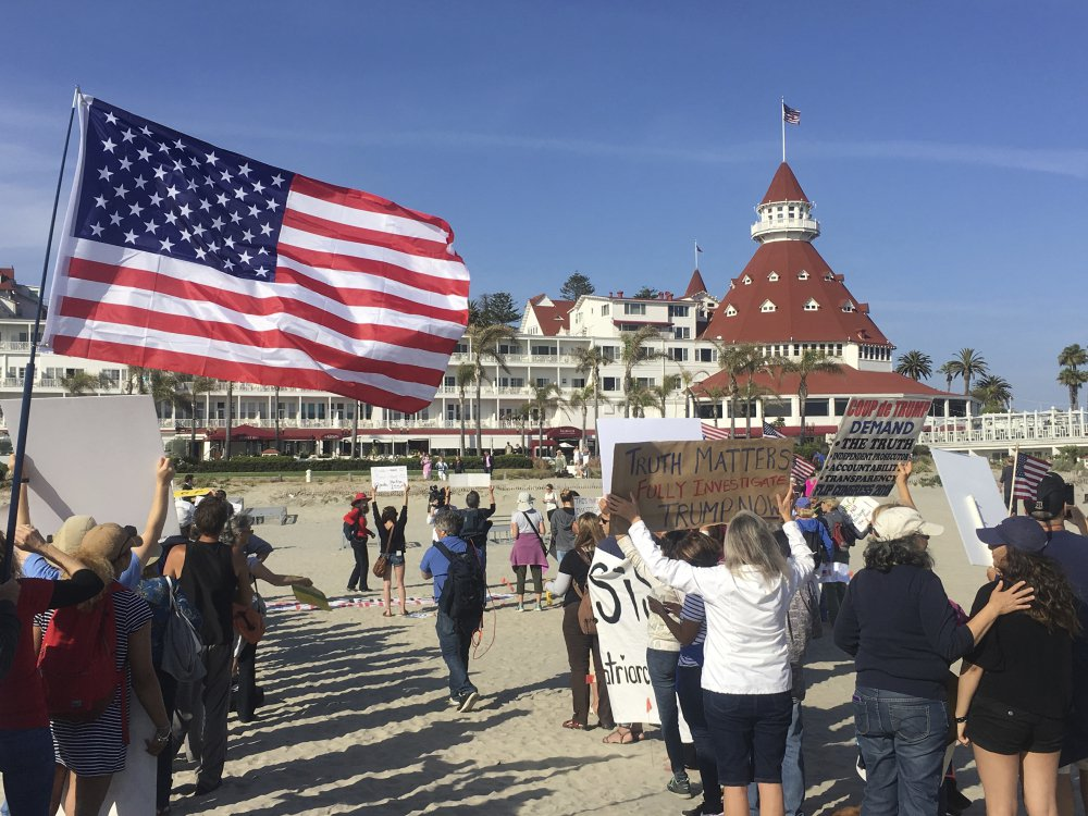 "Protesters gather Thursday outside the Republican National Committee spring meeting in Coronado, Calif. About 300 protesters marched on the beach, chanting, ""Hey, hey, ho, ho, Donald Trump has got to go!"""