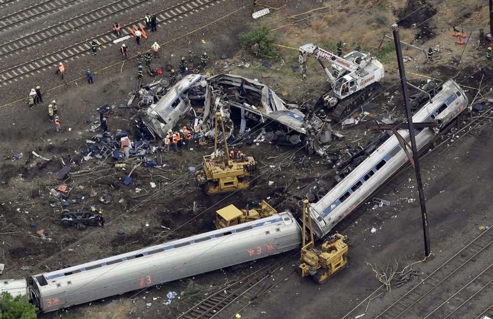Emergency personnel work near the wreckage of the Amtrak train that derailed in Philadelphia while taking a a 50 mph curve at 106 mph on May 12, 2015. Eight people and about 200 were injured.