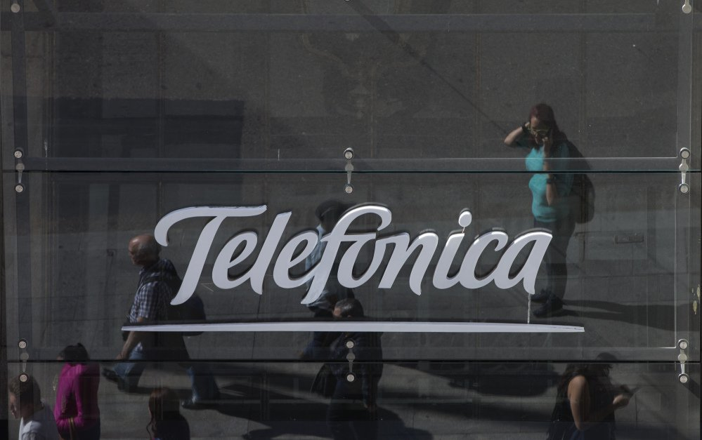 People are reflected in a glass sign of a Telefonica building in Madrid, Spain, on Saturday. The government said several companies including Telefonica had been targeted in a ransomware cyberattack that affected the Windows operating system of employees' computers.