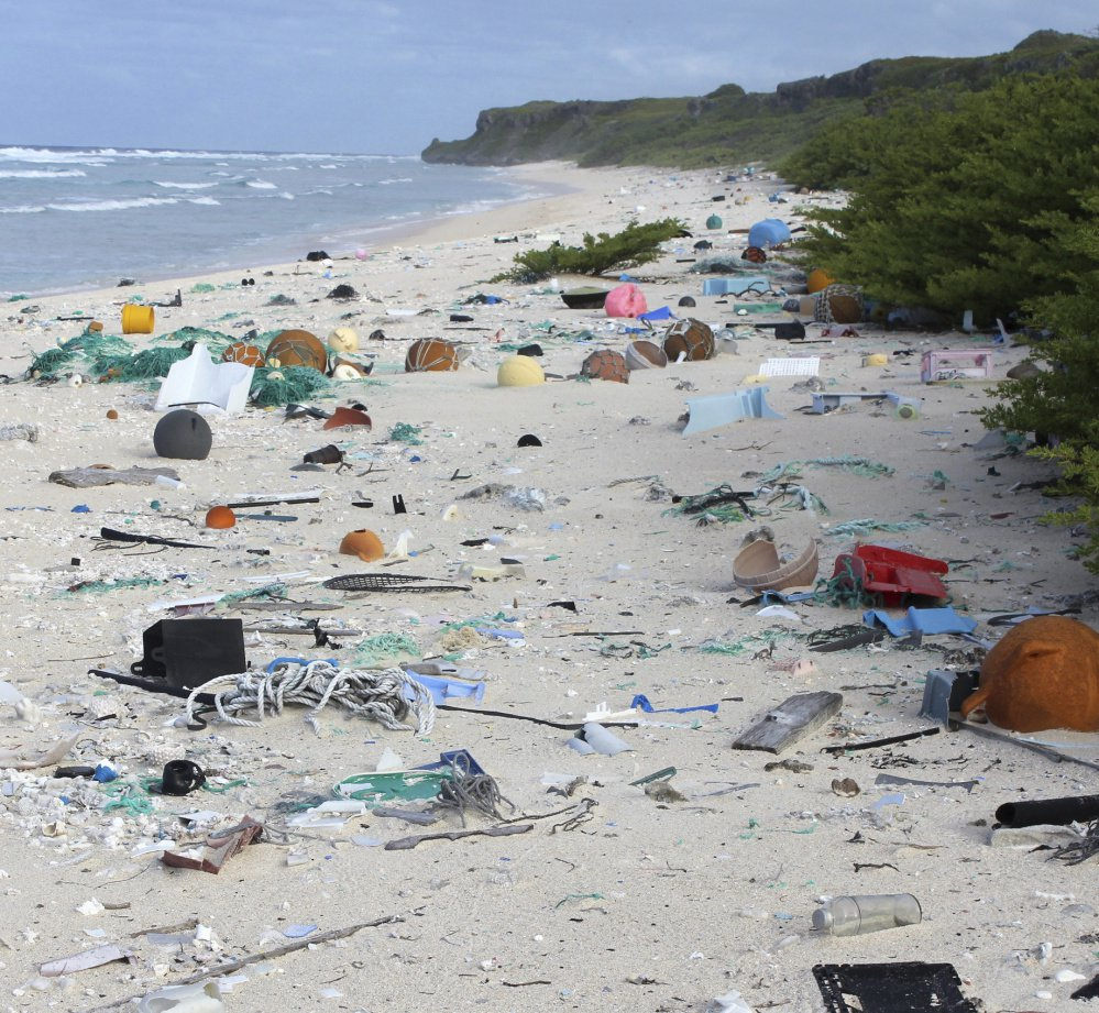 Above, a crab shelters in a piece of plastic debris on the beach of Henderson Island, at left. No humans live on the tiny atoll in the middle of the Pacific Ocean, but scientists say that as of 2015, an estimated 38 million pieces of trash had washed up there, with about 3,500 pieces of trash still arriving on the beaches daily.
