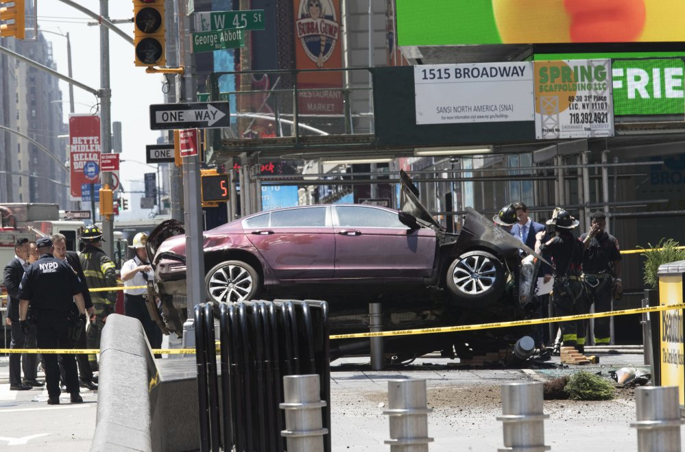 A car rests on a security barrier in New York's Times Square after plowing through a crowd of pedestrians on Thursday.