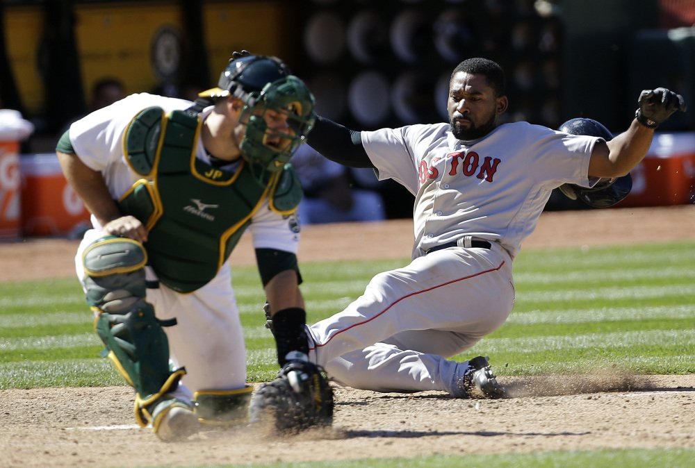 Jackie Bradley Jr. slides safely into home as Oakland catcher Josh Phegley fields the throw in the ninth inning of Boston's 12-3 win Sunday.