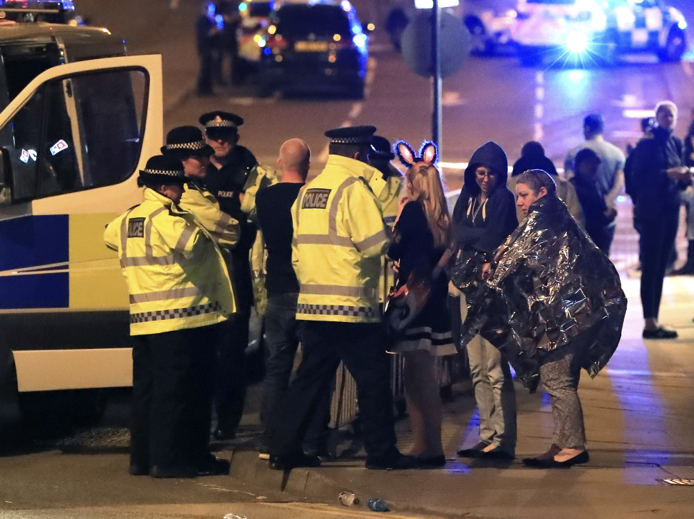 Emergency services personnel speak to people outside Manchester Arena in northern England after an explosion at the venue following an Ariana Grande concert Monday.