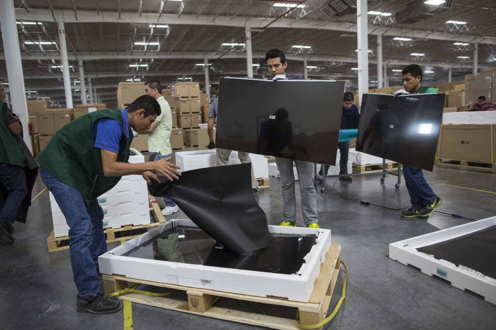 Workers check flat-screen screens for faults at Pantos logistics, an assembly plant in Reynosa, Mexico. Many of the workers make only $50 to $60 for a six-day work week and rely on a few hours of daily overtime to make ends meet.