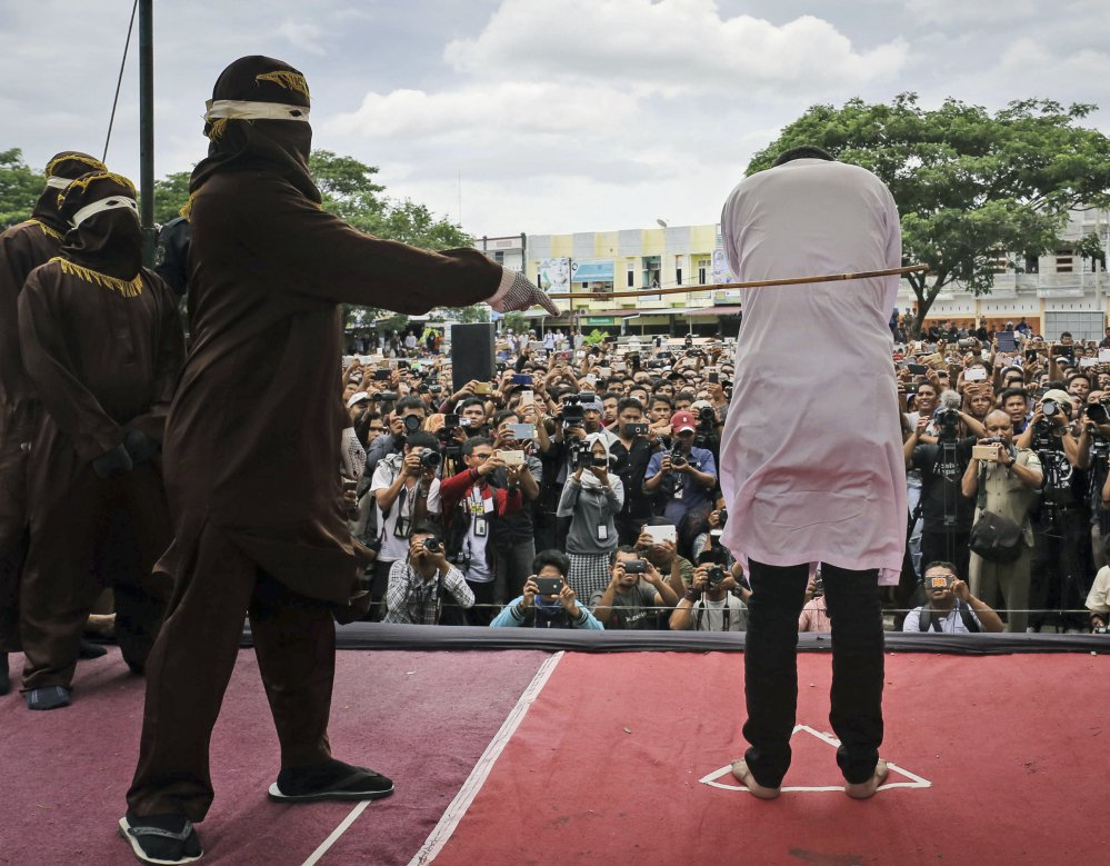 A team of five hooded Shariah law enforcers took turns caning two men for consensual gay sex in Banda Aceh, Indonesia, Tuesday. Each man was caned 83 times.