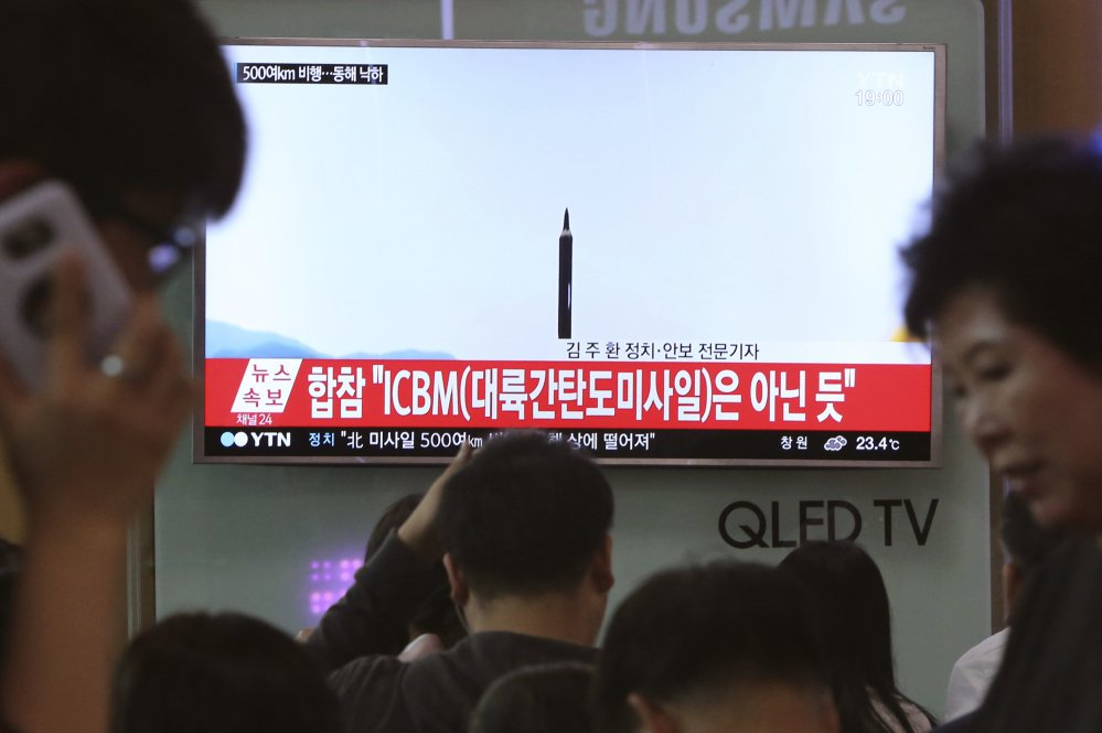 People watch a TV news program showing a file image of a missile launch conducted by North Korea, at the Seoul Railway Station in Seoul, South Korea, this month. With North Korea's nuclear missile threat in mind, the Pentagon is planning a missile defense test next week that for the first time will target an intercontinental-range missile.