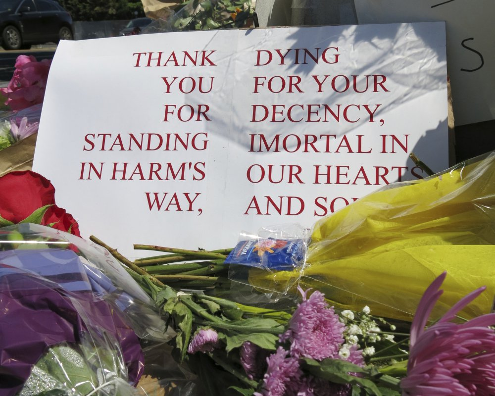 A sign of thanks rests against a traffic light pole at a memorial outside the transit center in Portland, Ore. on Saturday, May 27, 2017. People stopped with flowers, candles, signs and painted rocks for two bystanders who were stabbed to death Friday, while trying to stop a man who was yelling anti-Muslim slurs and acting aggressively toward two young women, including one wearing a Muslim head covering, on a light-trail train in Portland. Suspect Jeremy Joseph Christian, 35, was booked on suspicion of murder and attempted murder in the attack and will make a first court appearance Tuesday.