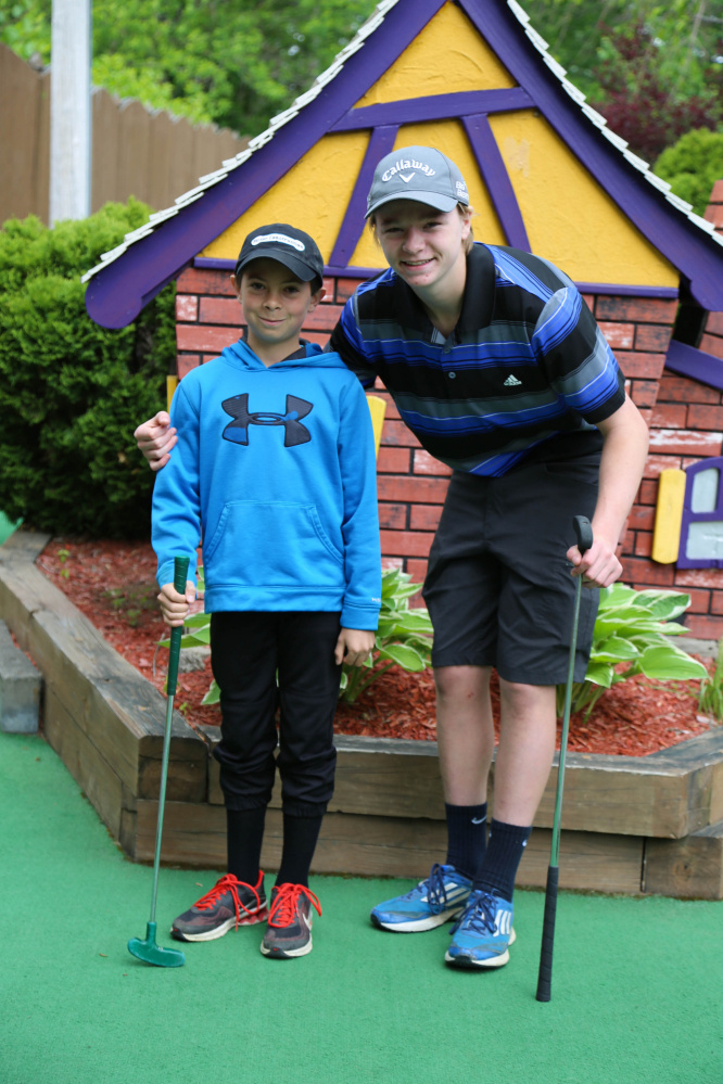 """Colby Charette, left, and his """"Little"""" Harrison Quimby, practice for the Putt 4 Cass fundraiser at Gifford's Famous Ice Cream & Mini Golf in Waterville."""