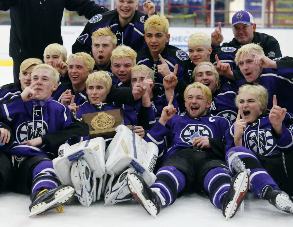 The Waterville hockey team celebrates after winning the Class B state championship in Lewiston this past season.