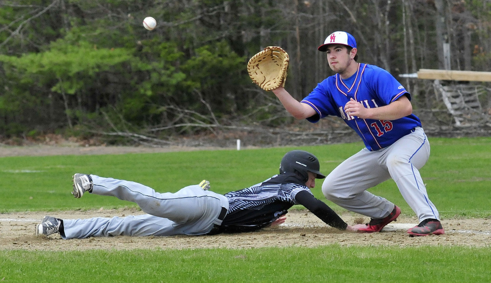 Bridgeway's Evan Bess makes it back to first base as Oak Hill's Reid Cote fields the throw Wednesday in North Anson.